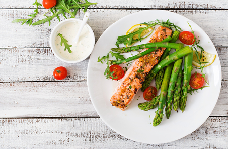 Baked salmon garnished with asparagus and tomatoes with herbs. Top view Standard-Bild