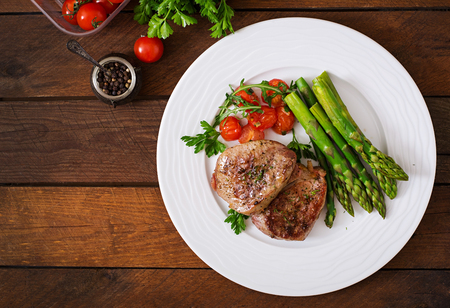 Barbecue grilled beef steak meat with asparagus and tomatoes. Top view