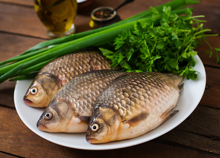 crucian carp: Three fresh raw crucian on a wooden background with herbs Stock Photo