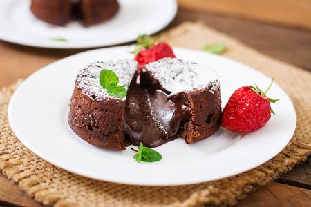 Chocolate fondant (cupcake) with strawberries and powdered sugar