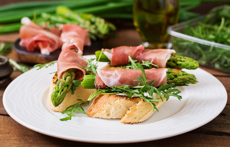 Toasts (sandwich) with asparagus, arugula and prosciutto Stock Photo