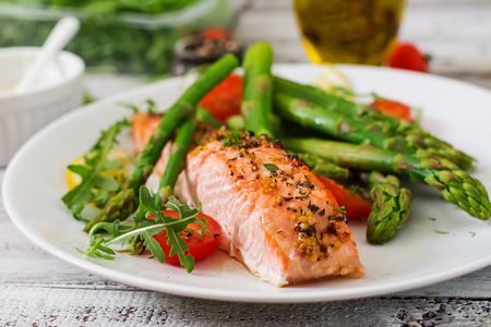 Baked salmon garnished with asparagus and tomatoes with herbs Reklamní fotografie