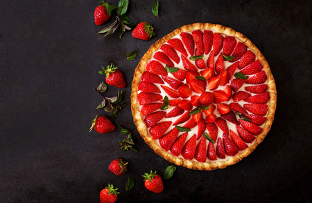 short crust pastry: Tart with strawberries and whipped cream decorated with mint leaves. Top view