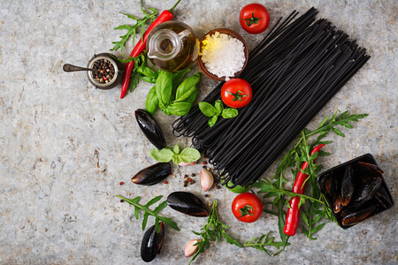 linguine pasta: Ingredients for black linguine pasta - tomato, basil, chili peppers and mussels. Top view