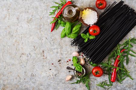 linguine pasta: Ingredients for black linguine pasta - tomato, basil, chili . Top view