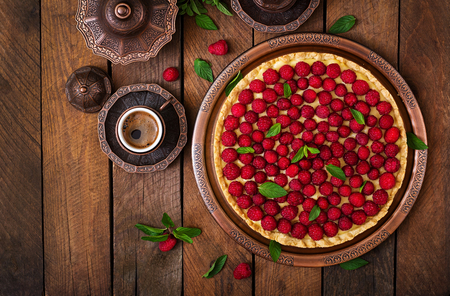 short crust pastry: Tart with raspberries and whipped cream decorated with mint leaves on a wooden background. Top view