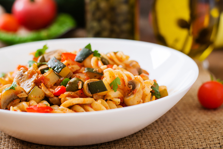 stirred: Vegetarian Vegetable pasta Fusilli with zucchini, mushrooms and capers in white bowl on wooden table Stock Photo