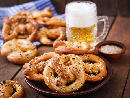 Oktoberfest salted soft pretzels in a bowl and beer from Germany on wooden background. Stock Photo