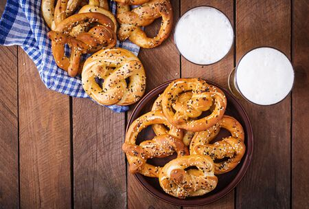 Oktoberfest salted soft pretzels in a bowl and beer from Germany on wooden background. Top view