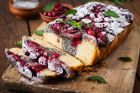 Cherry poppy seed cake dusted with powdered sugar on a wooden table Stock Photo