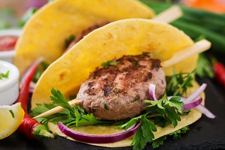 tacos de tortillas con kebab apetitoso (albóndigas) y la salsa en el fondo negro