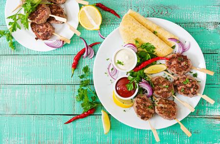 Kebab appetitoso kofta (polpette di carne) con salsa e tortillas tacos su un piatto bianco. Vista dall'alto Archivio Fotografico - 62297093