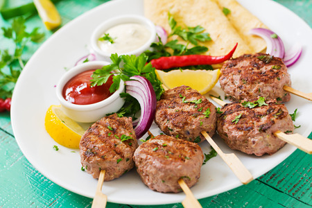 tortillas: Appetizing kofta kebab (meatballs) with sauce and tortillas tacos on a white plate Stock Photo