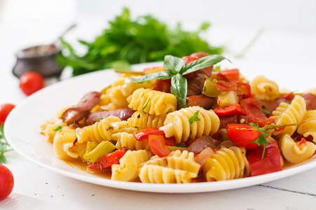 stirred: Pasta with tomato sauce with sausage, tomatoes, green basil decorated in white plate on a wooden background.
