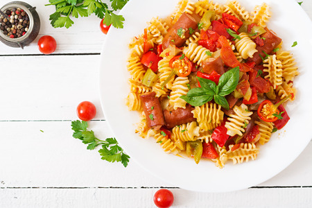 stirred: Pasta with tomato sauce with sausage, tomatoes, green basil decorated in white plate on a wooden background. Top view