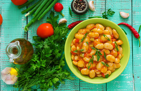 Steamed white beans with vegetables in tomato sauce. Top view