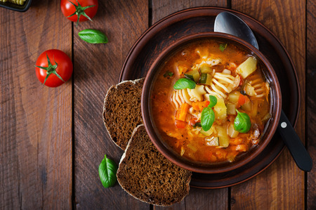 vegetable soup: Minestrone, italian vegetable soup with pasta on wooden table. Top view
