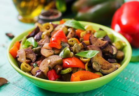 Caliente guiso picante de la berenjena, pimiento, aceitunas y alcaparras con hojas de albahaca.