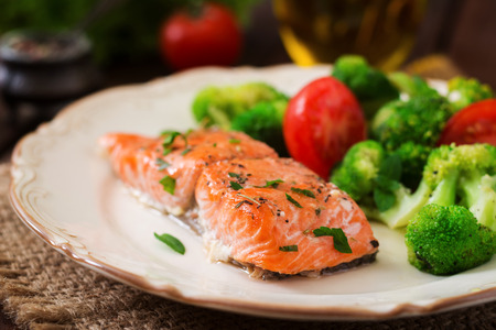 Baked fish salmon garnished with broccoli and tomato. Dietary menu. Fish menu. Seafood - salmon. Stock Photo