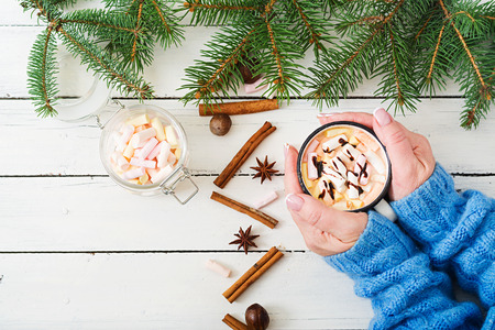 Female hand holding a cup of hot cocoa or chocolate with marshmallow on a light wooden background. Flat lay. Top view