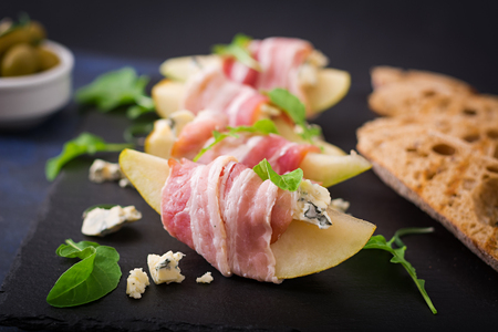 roquefort: Appetizer with pear, blue cheese, prosciutto ham and toast for holidays on a dark plate.