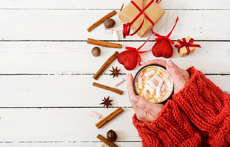 Female hand holding a cup of hot cocoa or chocolate with marshmallow on a light wooden background. Flat lay. Top view. Valentines day.