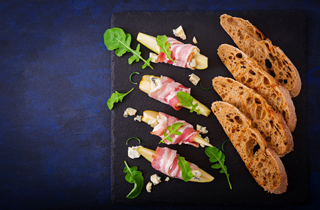roquefort: Appetizer with pear, prosciutto, ham, blue cheese for holidays and toast on a dark background. Flat lay. Top view.