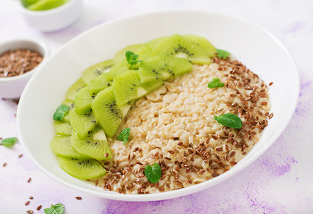 Tasty and healthy oatmeal porridge with kiwi and flax seeds. Healthy breakfast. Fitness food. Proper nutrition Stock Photo