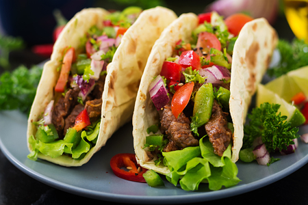 Mexican tacos with beef in tomato sauce and salsa