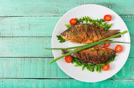 Fried fish carp and fresh vegetable salad on wooden background. Flat lay. Top view Reklamní fotografie - 81238609