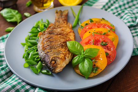 Fried fish carp and fresh vegetable salad on wooden background. Stock Photo