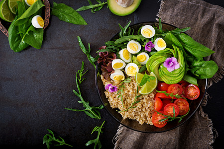 Diet menu. Healthy salad of fresh vegetables - tomatoes, avocado, arugula, egg, spinach and quinoa on bowl. Flat lay. Top view.