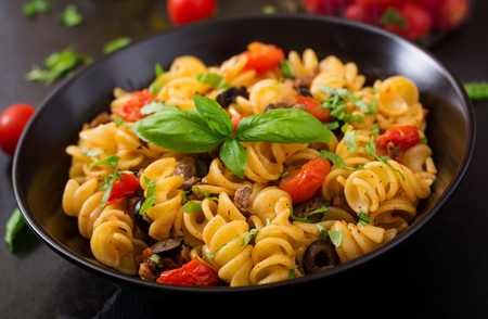 stirred: Pasta Fusilli  with tomatoes, beef and basil in black bowl on table.
