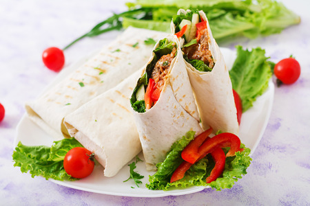 Burritos wraps with minced beef and vegetables on a light background. Stock Photo