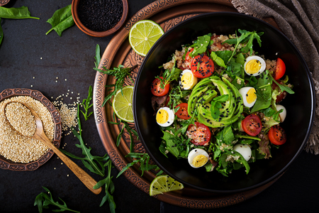 Diet menu. Healthy salad of fresh vegetables - tomatoes, avocado, arugula, egg, spinach and quinoa on a bowl. Flat lay. Top view.