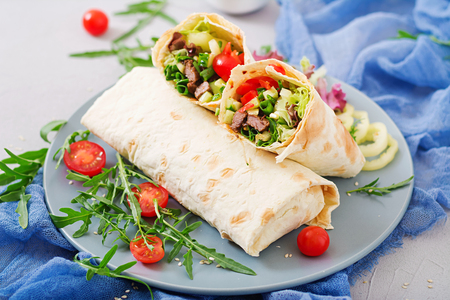Shawarma from juicy beef, lettuce, tomatoes, cucumbers, paprika and onion in pita bread. Diet menu. Stock Photo