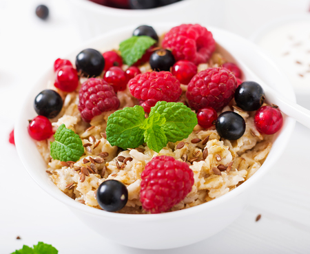 Tasty and healthy oatmeal porridge with berry, flax seeds and yogurt. Healthy breakfast. Fitness food. Proper nutrition. Stock Photo