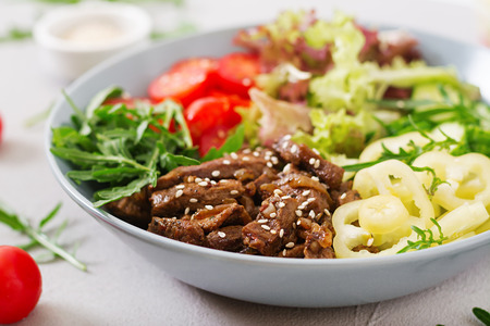 Salad with beef teriyaki and fresh vegetables - tomatoes, cucumbers, paprika, arugula and lettuce in bowl. Stock Photo