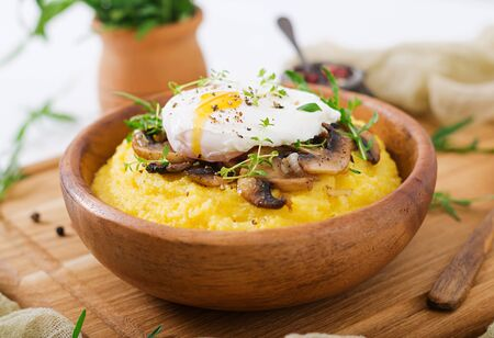 Breakfast. Polenta with mushrooms and poached egg Stock Photo - 82112075