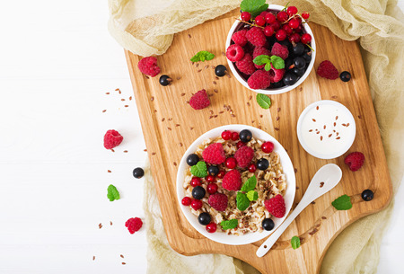 Tasty and healthy oatmeal porridge with berry, flax seeds and yogurt. Healthy breakfast. Fitness food. Proper nutrition. Flat lay. Top view. Stock Photo