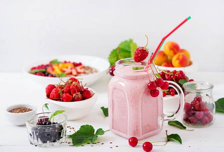 Yoghurt-strawberry smoothies in a jar on a white background. Stock Photo