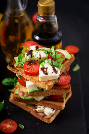 Sandwich toasts with tomatoes, mozzarella, avocado and basil with balsamic vinegar. Stock Photo