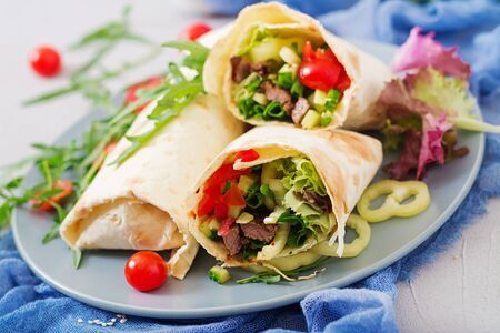 Shawarma from juicy beef, lettuce, tomatoes, cucumbers, paprika and onion in pita bread. Diet menu. Stock Photo - 82112197