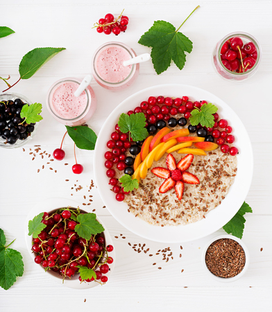 Tasty and healthy oatmeal porridge with berry, flax seeds and smoothies. Healthy breakfast. Fitness food. Proper nutrition. Top view. Flat lay. Stock Photo