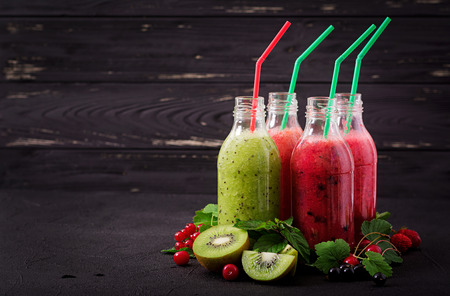 Fresh healthy smoothies from different berries on a dark background. Stock Photo