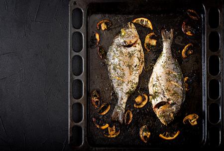 Baked dorado fish  in garlic dill sauce with mushrooms and lemon.Flat lay.Top view. Stock Photo