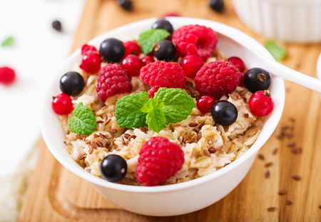 Tasty and healthy oatmeal porridge with berry, flax seeds and yogurt. Healthy breakfast. Fitness food. Proper nutrition Stock Photo - 82112222