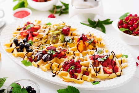Variety of Belgian wafers with berries, chocolate and syrup. Stock Photo
