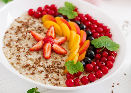 Tasty and healthy oatmeal porridge with berry, flax seeds and smoothies. Healthy breakfast. Fitness food. Proper nutrition