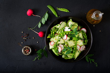 Fresh salad of cucumbers, radishes, green peas and herbs. Flat lay. Top view